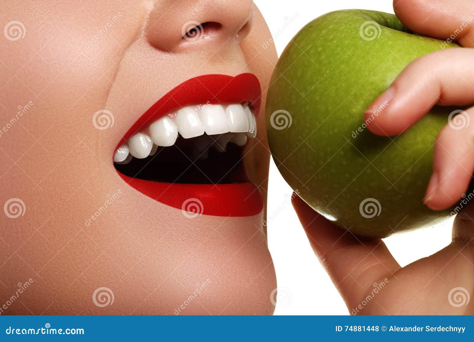 Close up da cara de uma mulher que come uma maçã verde, AG isolado