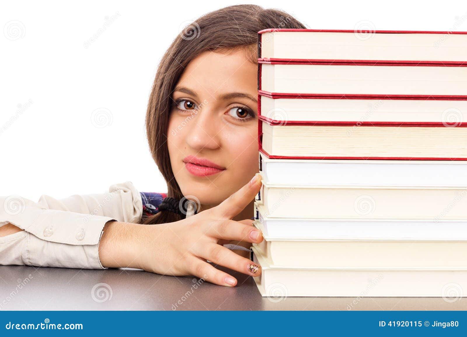 Close up da cara do estudante atrás da pilha de livros