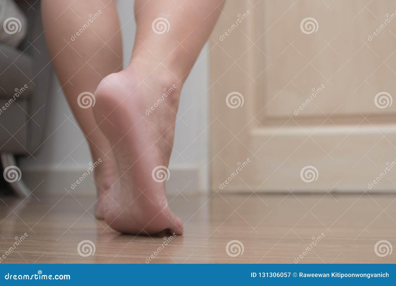 Close up da dor fêmea do salto do pé direito, fasciitis relativo à planta do pé