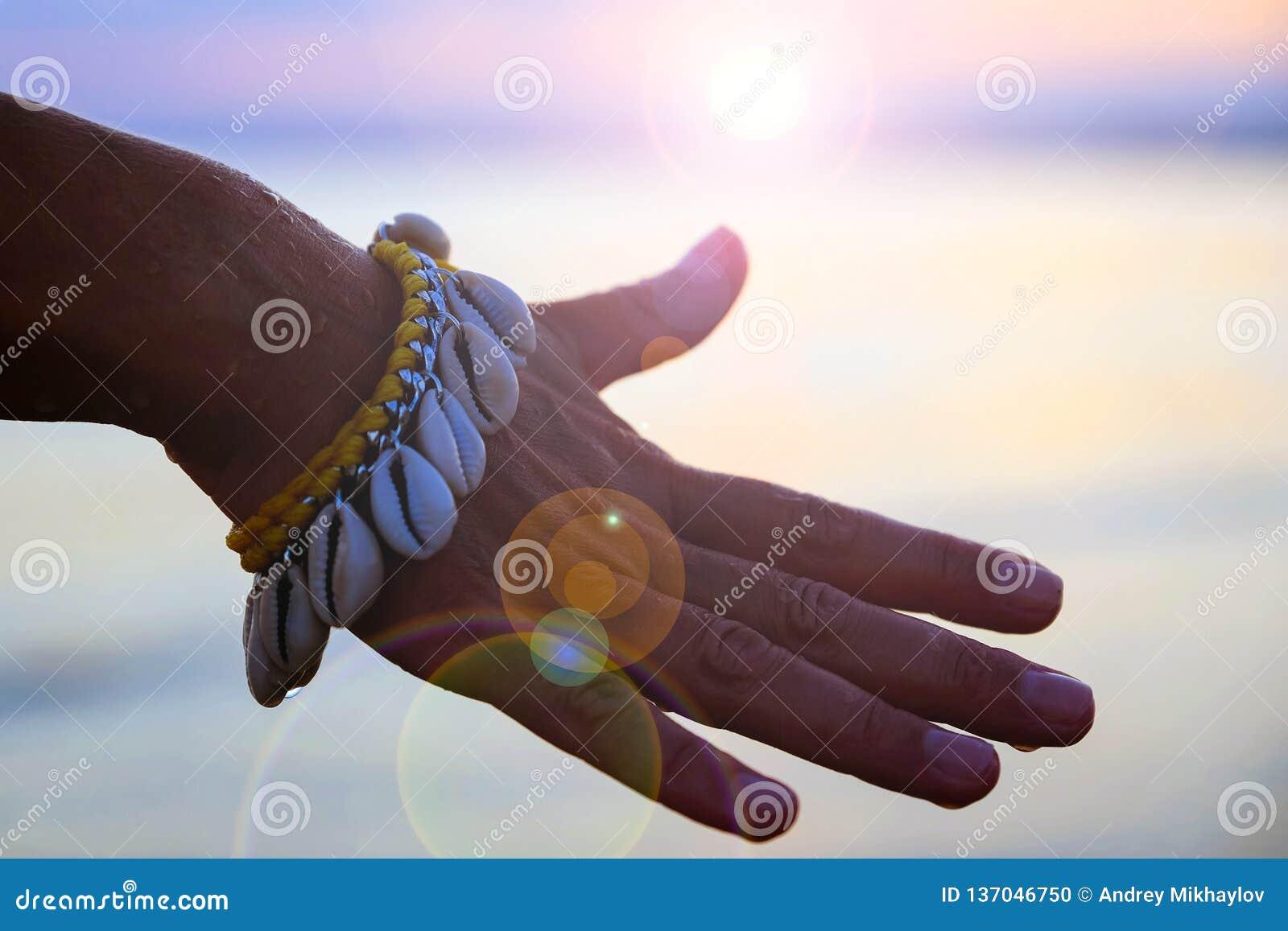 Close-up da mão de uma menina delicada com um bracelete feito das conchas do mar no fundo da água Mão no fundo do por do sol