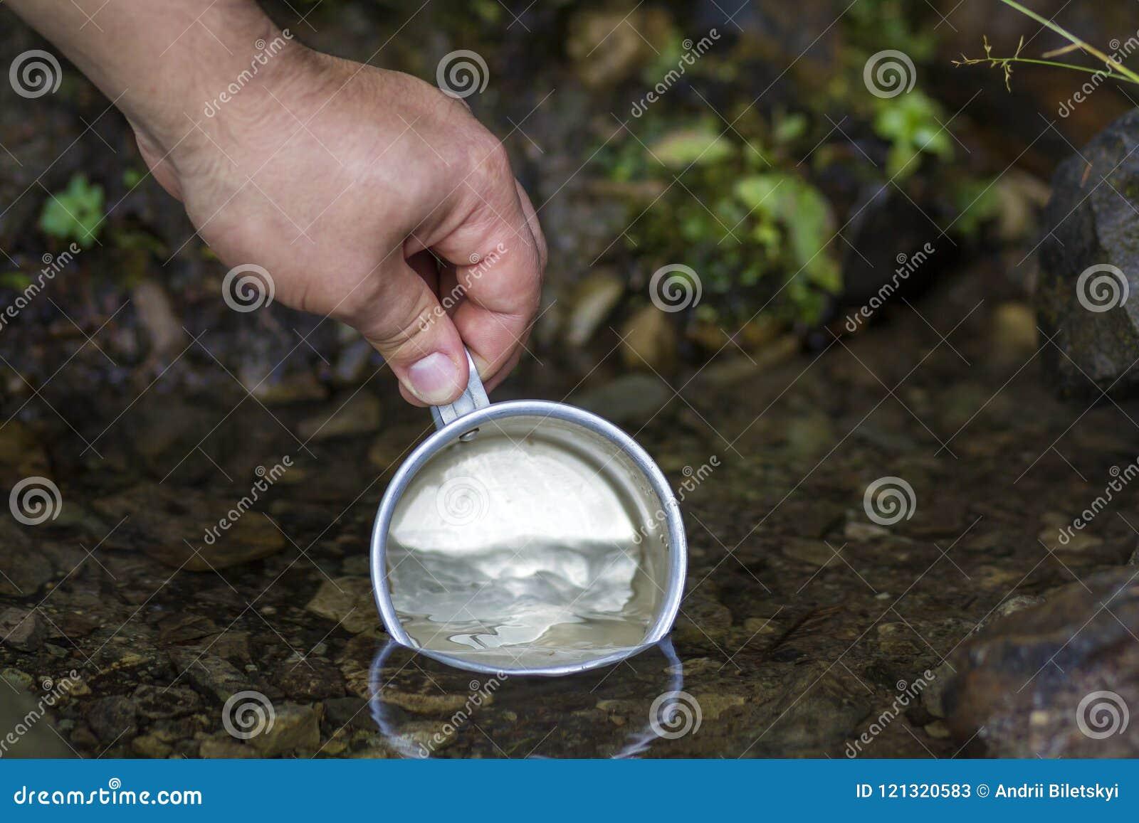 Close-up da mão do homem com o copo de alumínio do turista que escava o franco limpo