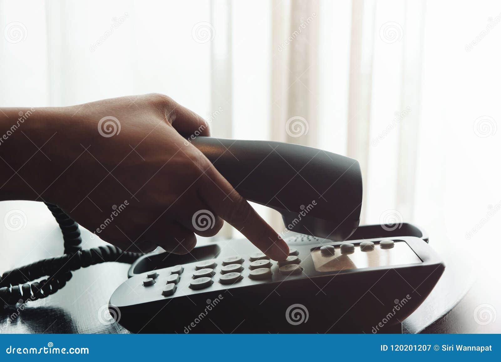 Close-up da mão do ` s da mulher usando um telefone no nea da casa ou do hotel