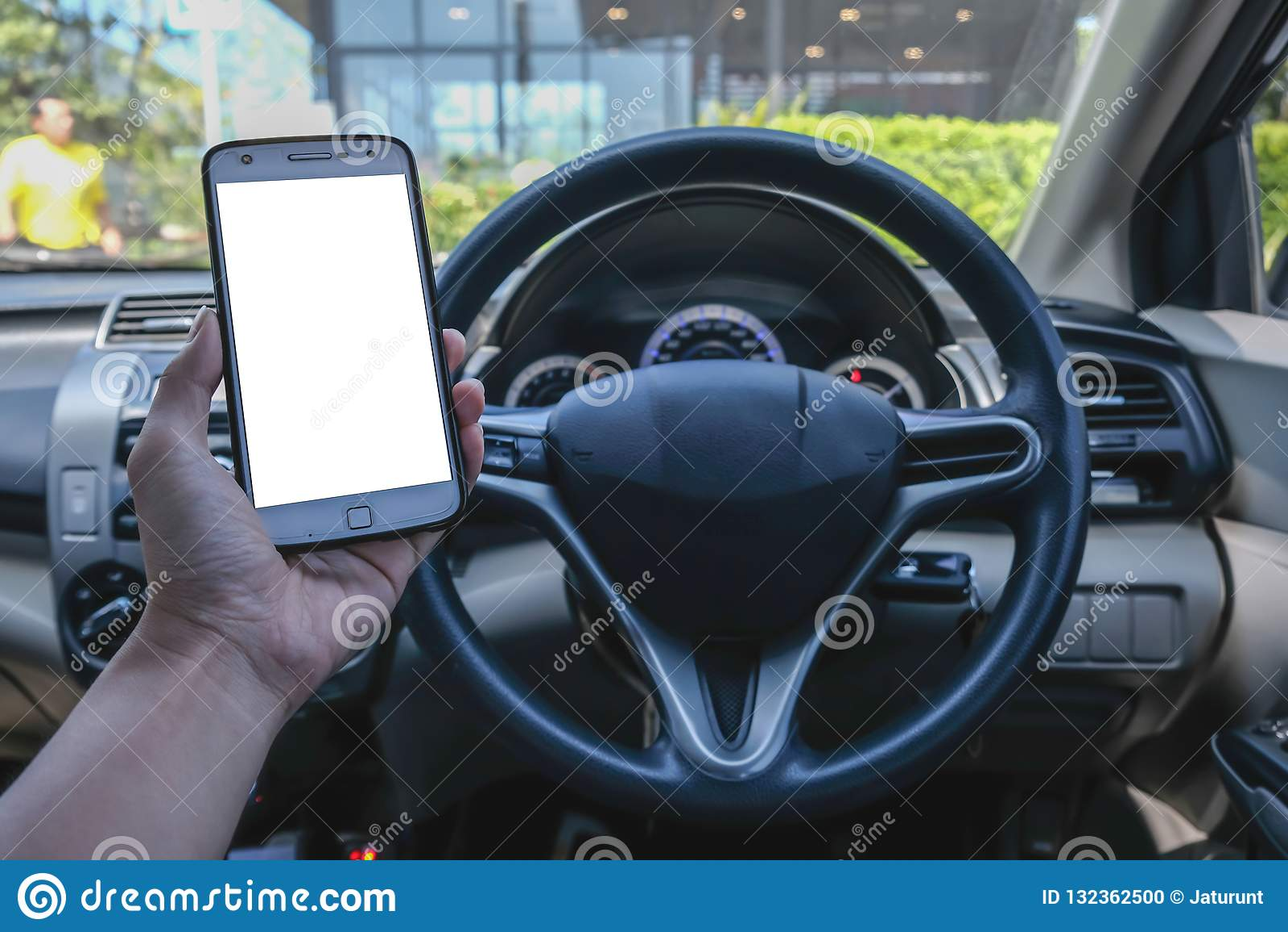 Close-up da mão masculina do motorista usando o smartphone no carro no dia ensolarado