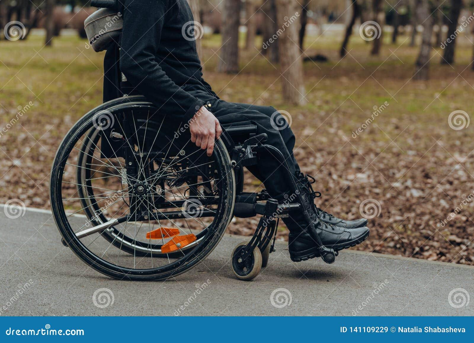Close-up da mão masculina na roda da cadeira de rodas durante a caminhada no parque