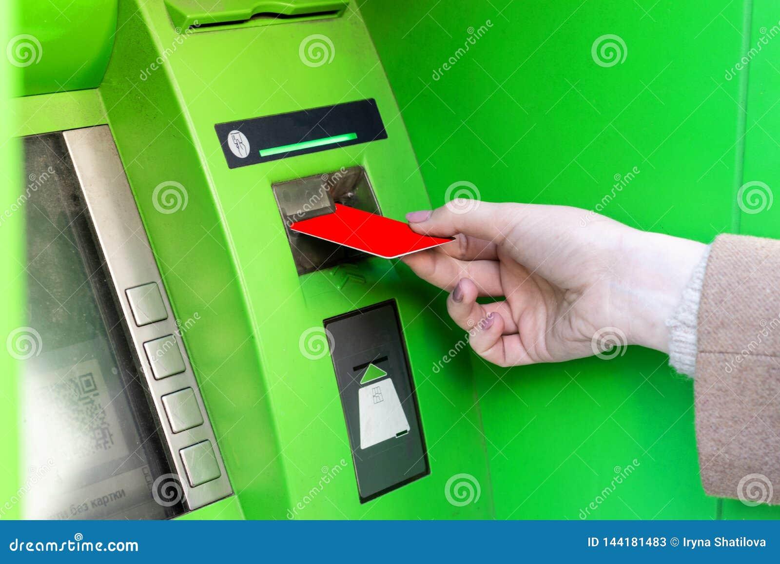 Close-up da mulher de sorriso da mulher que retira o dinheiro do cartão de crédito no ATM