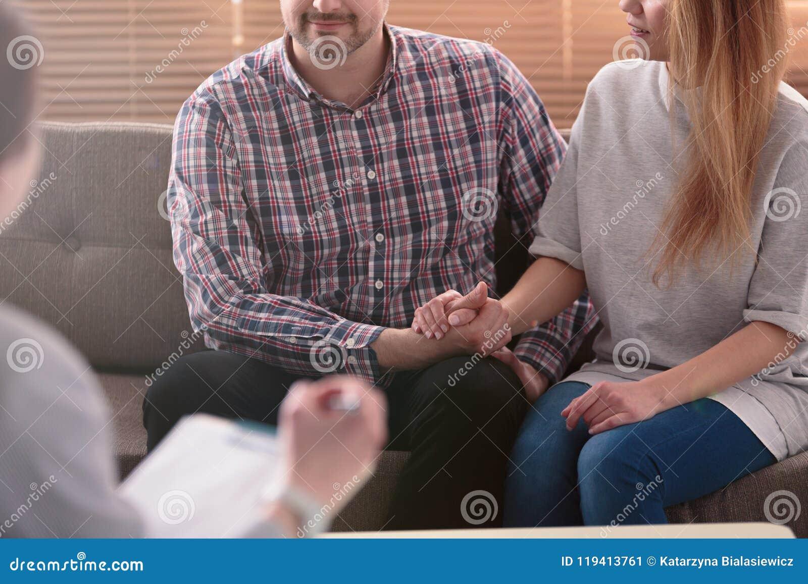 Close-up da mulher e do homem que guardam as mãos em um sofá durante um psyc