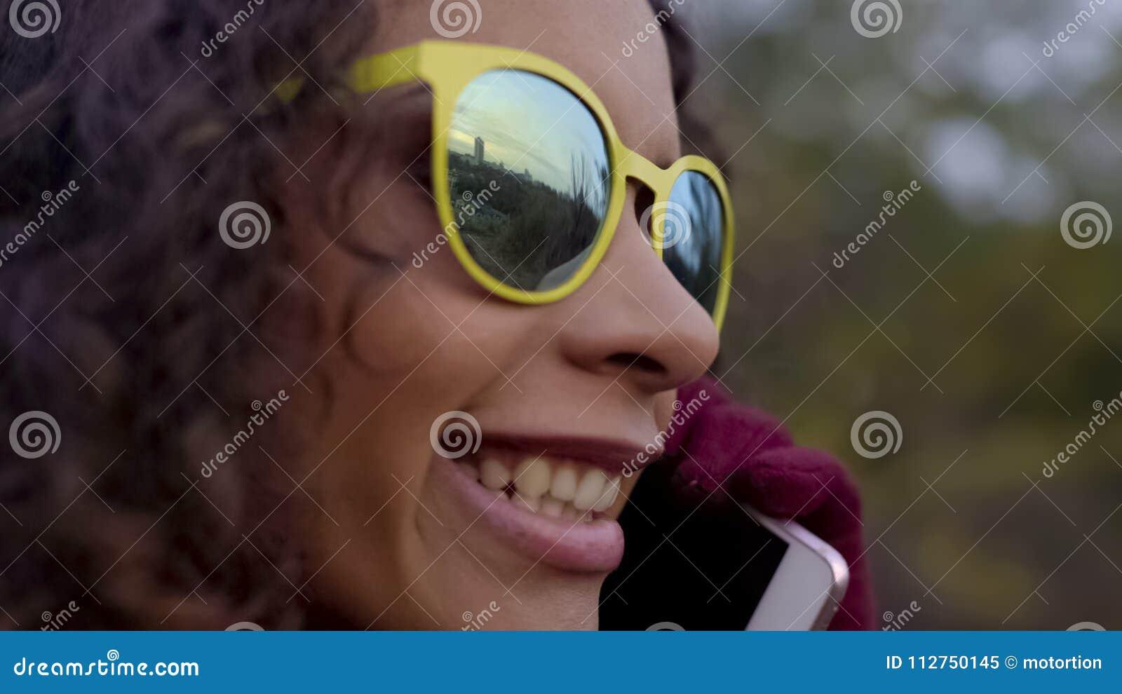 Close up da senhora feliz biracial nos óculos de sol que fala sobre o telefone, reflexão da cidade