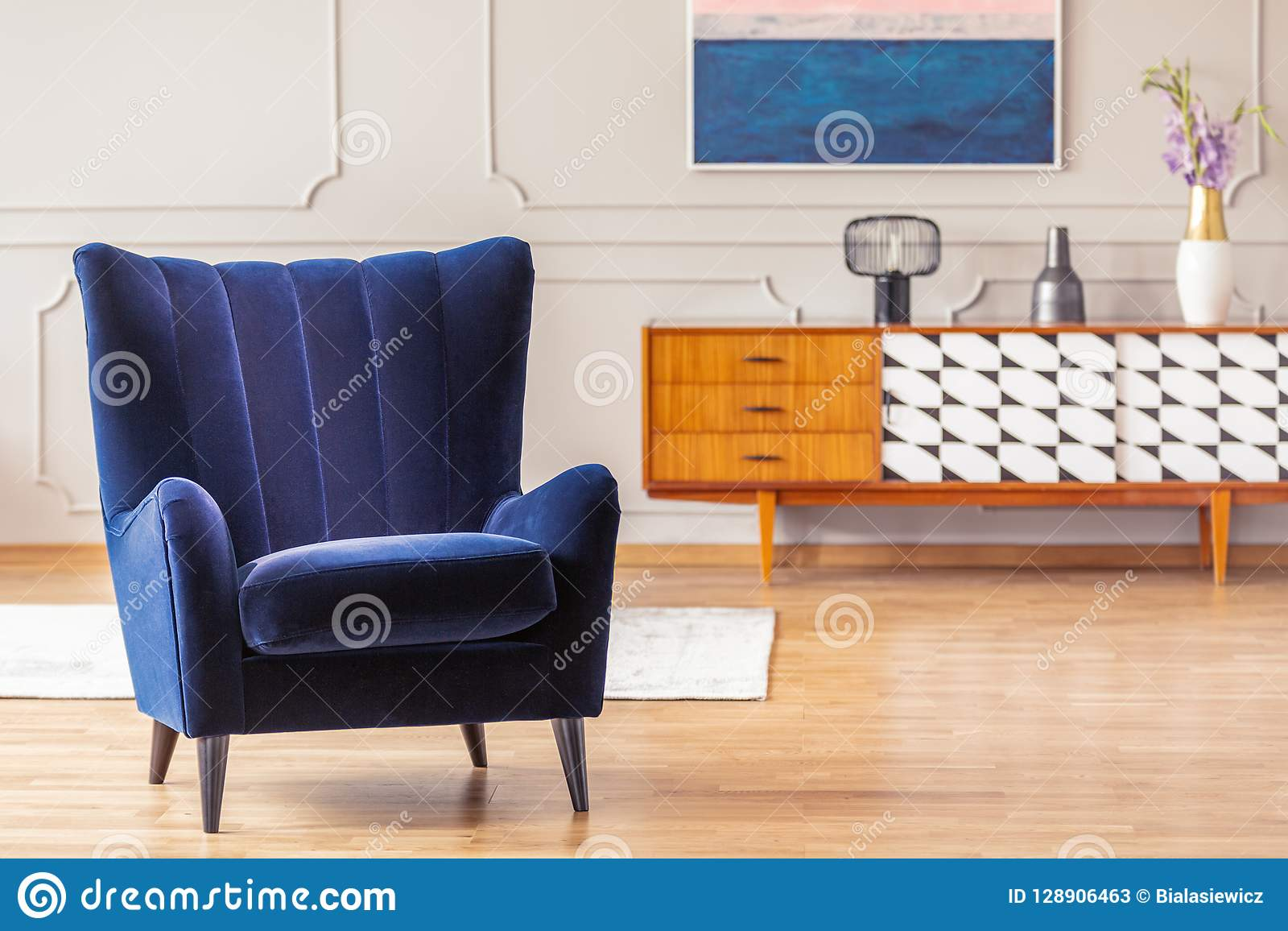 Dark blue armchair with a vintage cabinet in the background in a living room interior