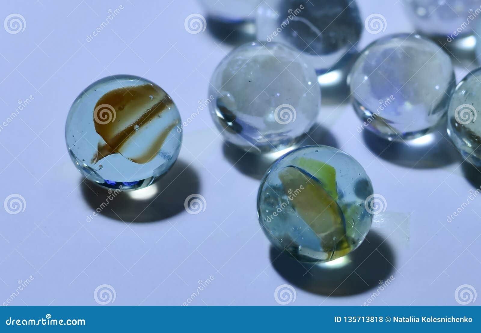 Close-up das bolas transparentes de vidro com as decorações multi-coloridas incomuns para dentro com um fundo borrado macio
