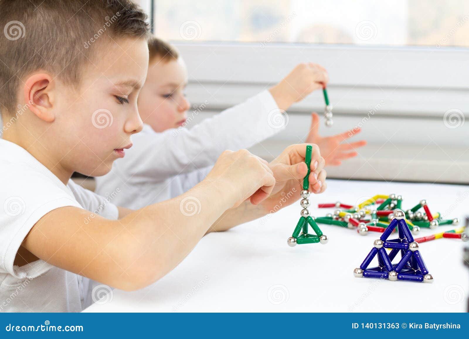 Close-up das crianças que jogam o jogo de mesa ao sentar-se na tabela em casa, em varas e em bolas magnéticas para o desenvolvime