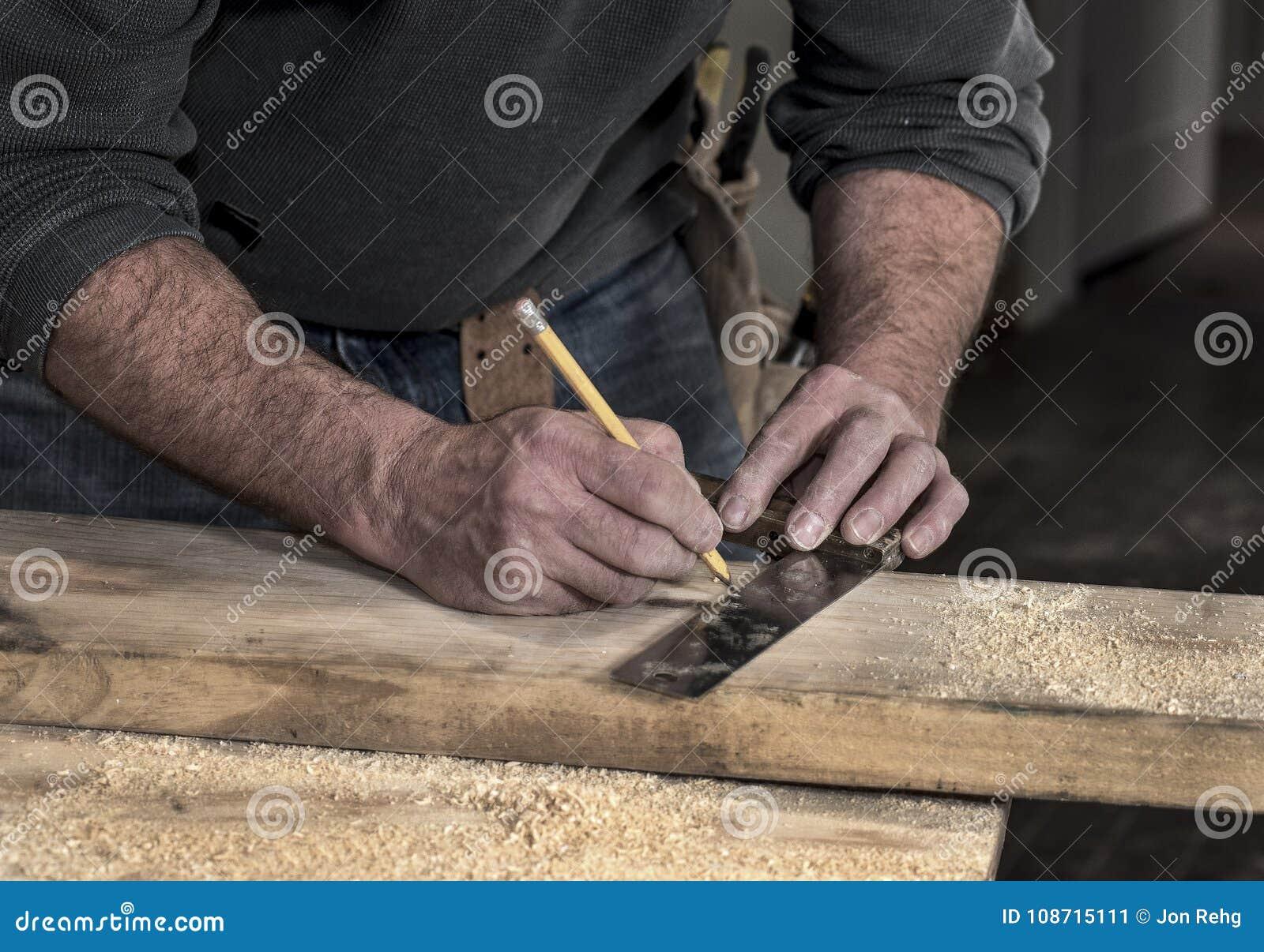 Close up das mãos ásperas ásperas do ` s do carpinteiro usando um lápis e um quadrado velho para marcar uma linha na placa de mad