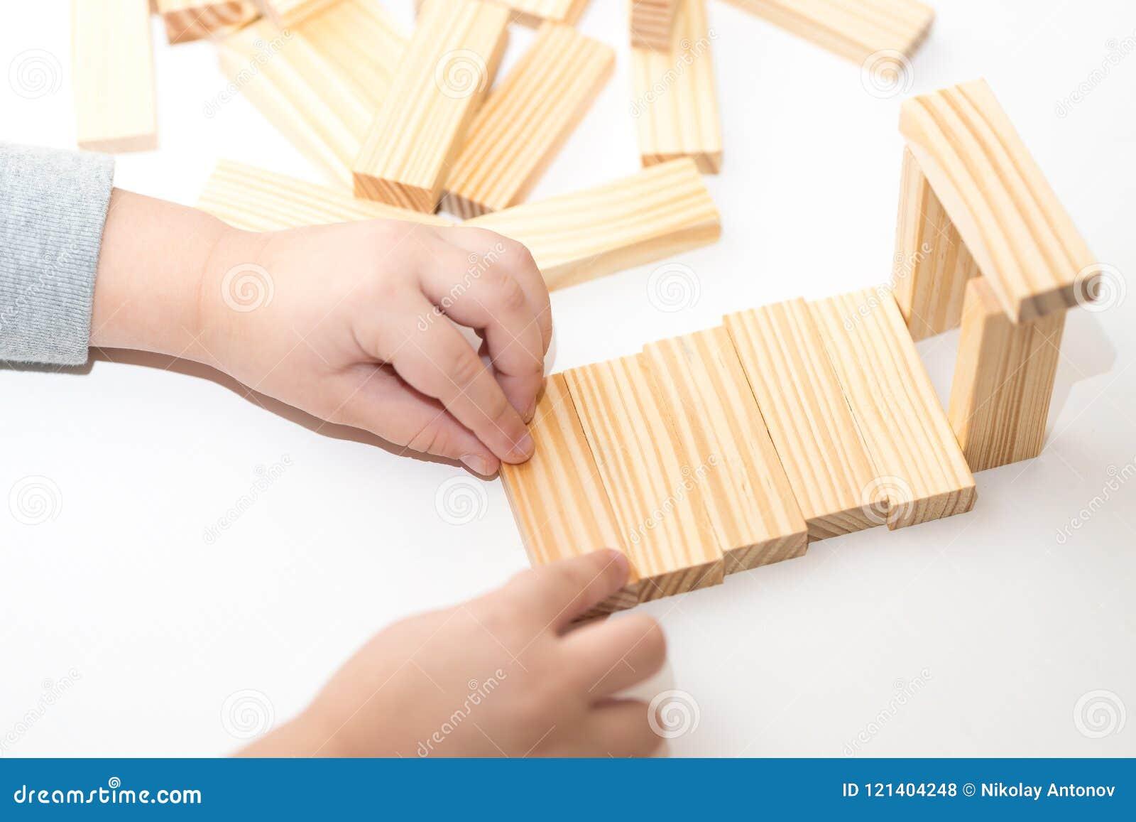 Close up das mãos das crianças que jogam com blocos de madeira e a casa de construção Conceito da instrução