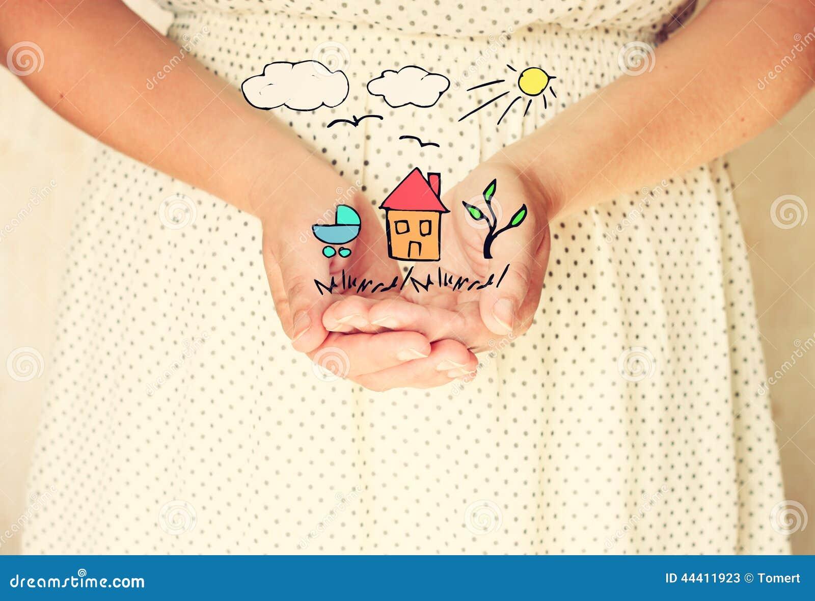 Close up das mãos da jovem mulher entrega estendido na forma colocada esboços da árvore e dos pássaros da casa como sonhos da ima
