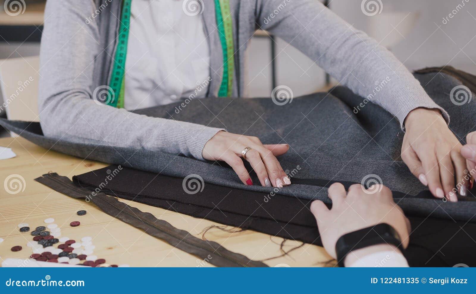 Close-up das mãos dos desenhadores de moda costurados que trabalham com materiais, eles que sentam-se na oficina bonita com