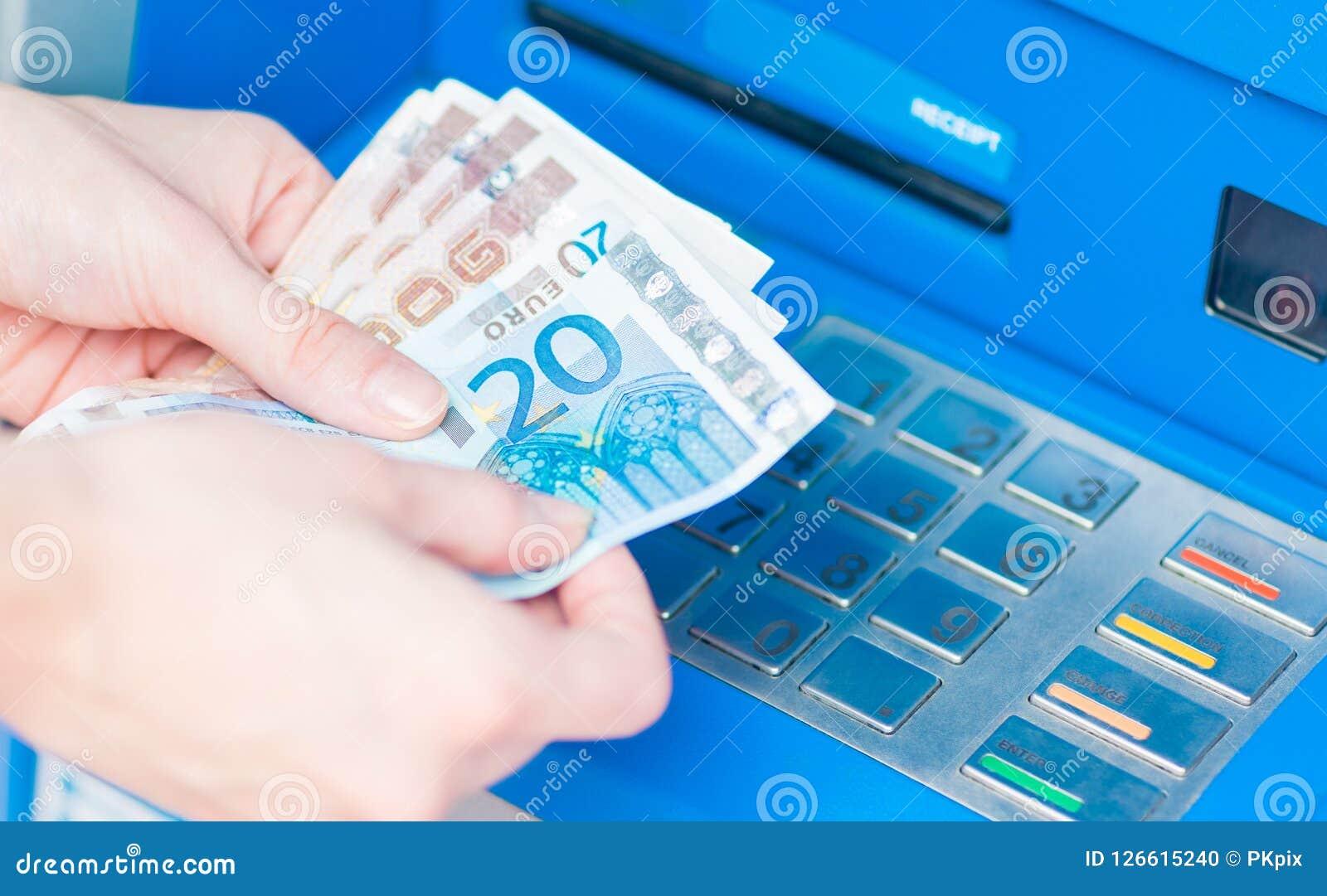 Close-up das mãos que contam as contas do Euro retiradas do ATM