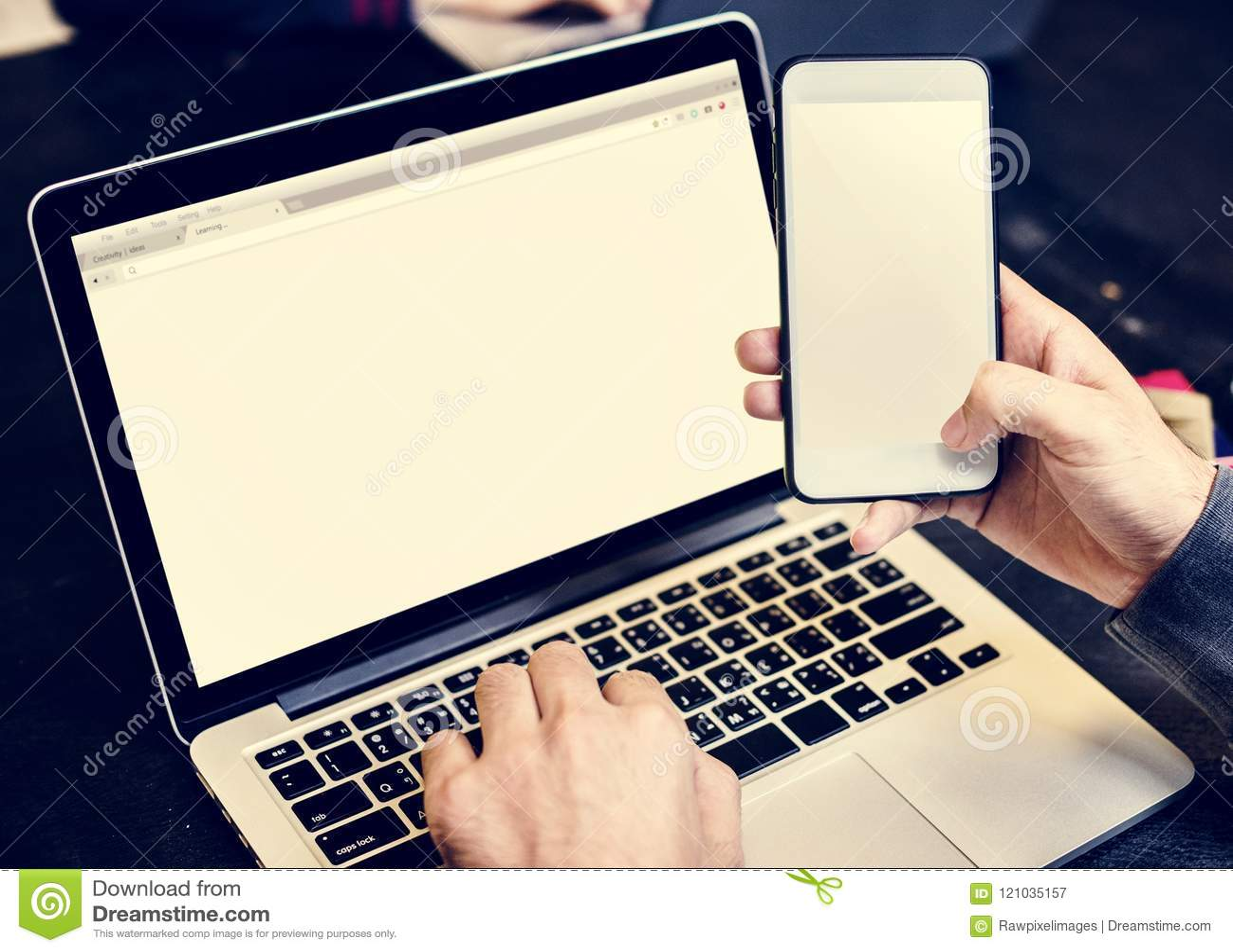 Close up das mãos que guardam o telefone celular com fundo do portátil do computador
