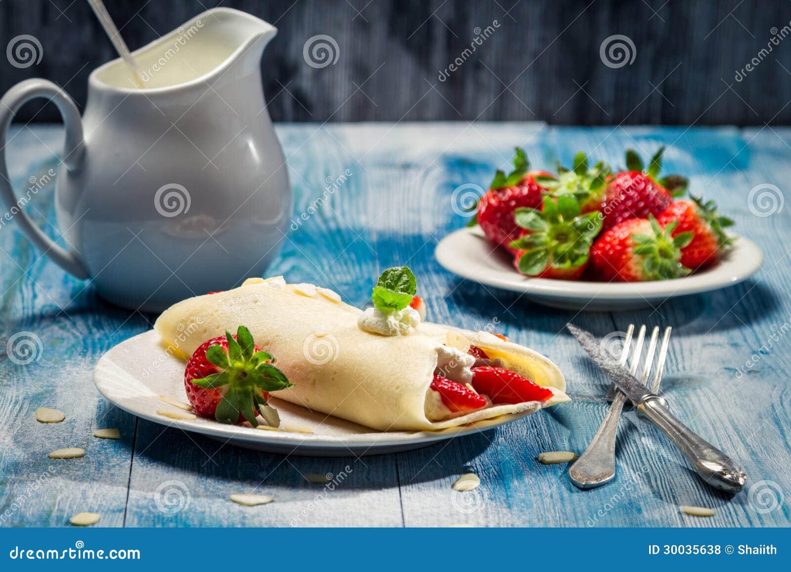 Close up das panquecas com morangos e creme chicoteado