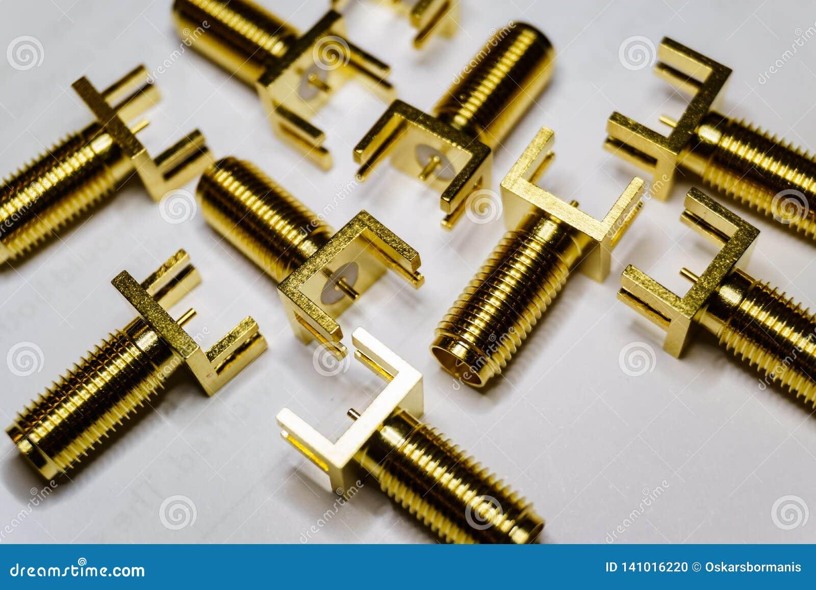 Close-up de componentes chapeados ouro dispersados da eletrônica dos conectores machos de SMA no fundo branco no teste padrão ale