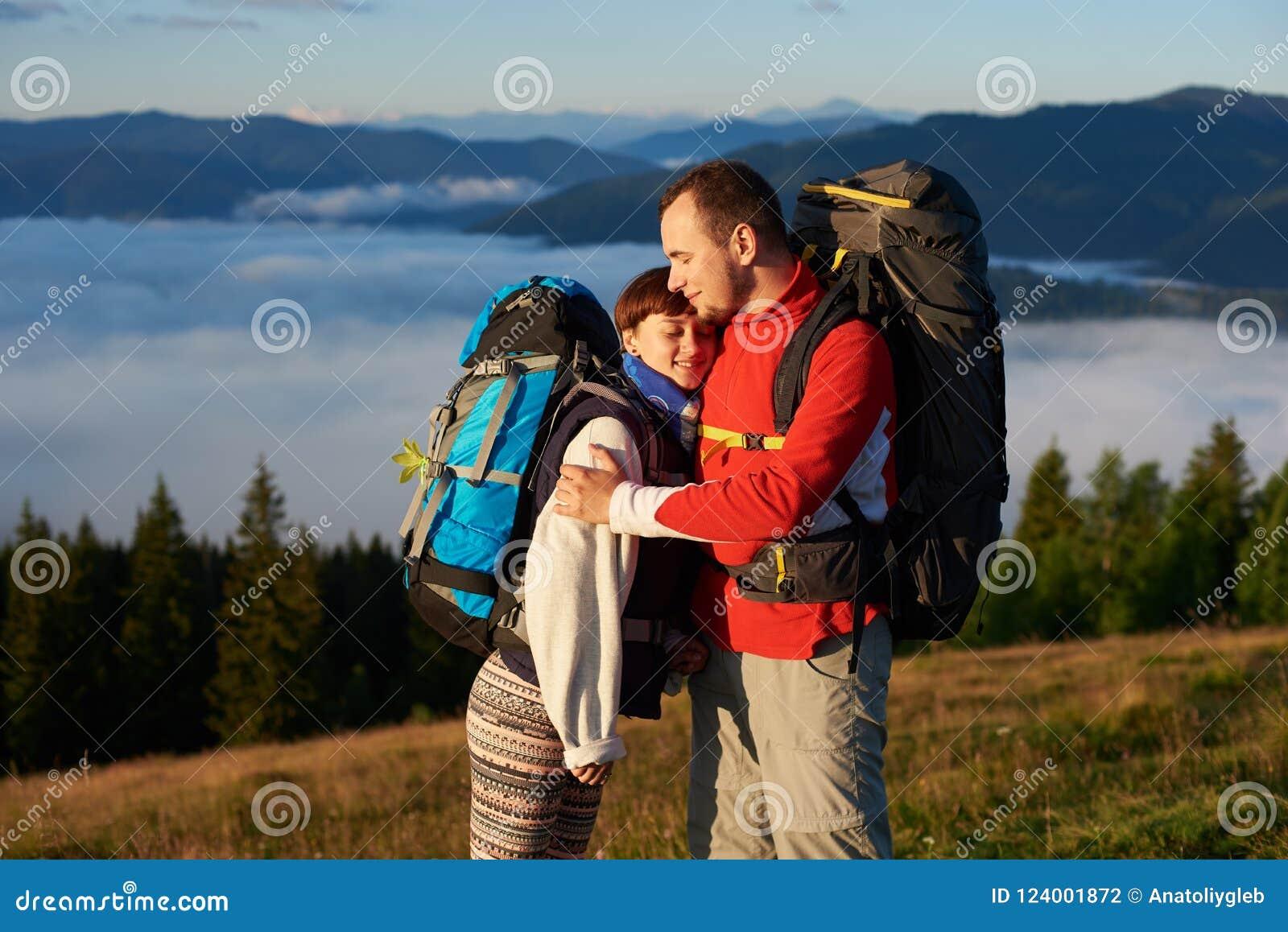 Close-up de masculino e da fêmea que abraçam-se que aprecia raios do por do sol nas montanhas