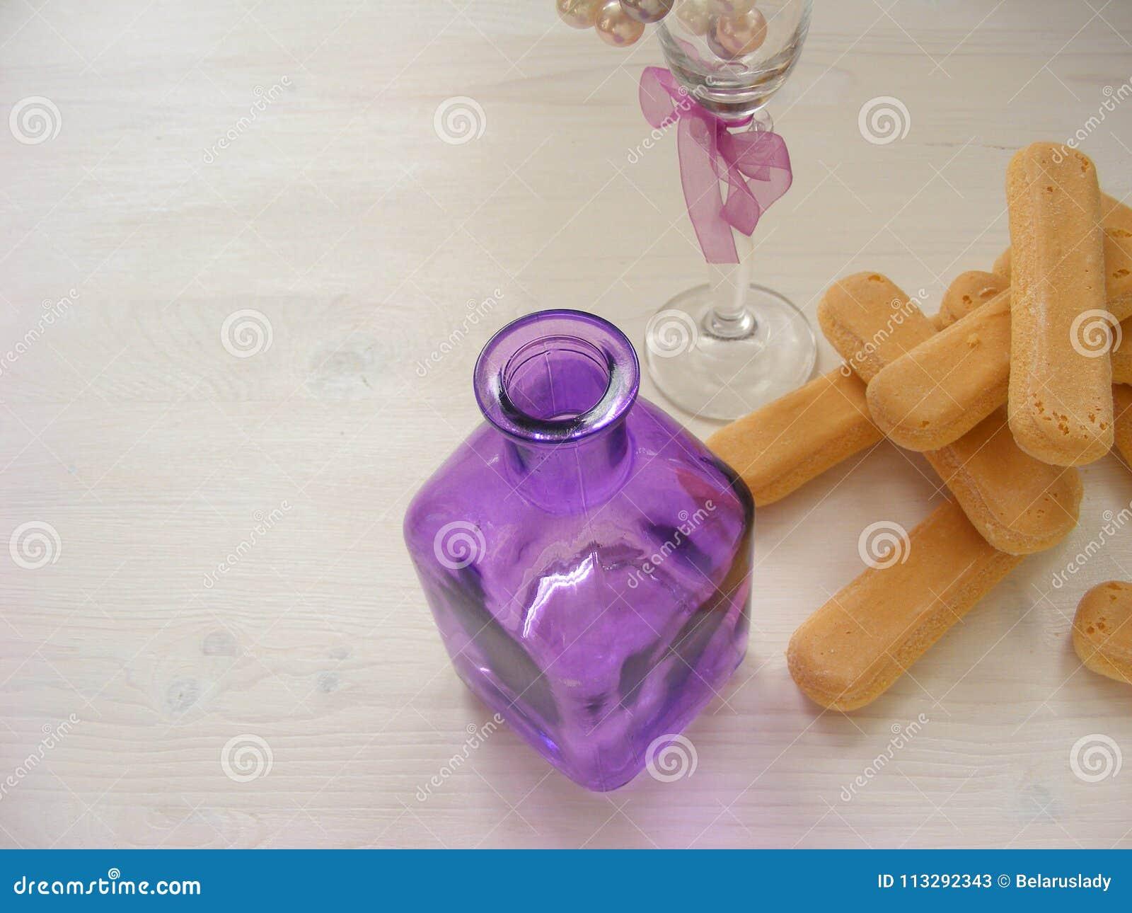 Close up de muitas cookies de Savoiardi com garrafa e vidro violetas em uma tabela branca do vintage com espaço da cópia