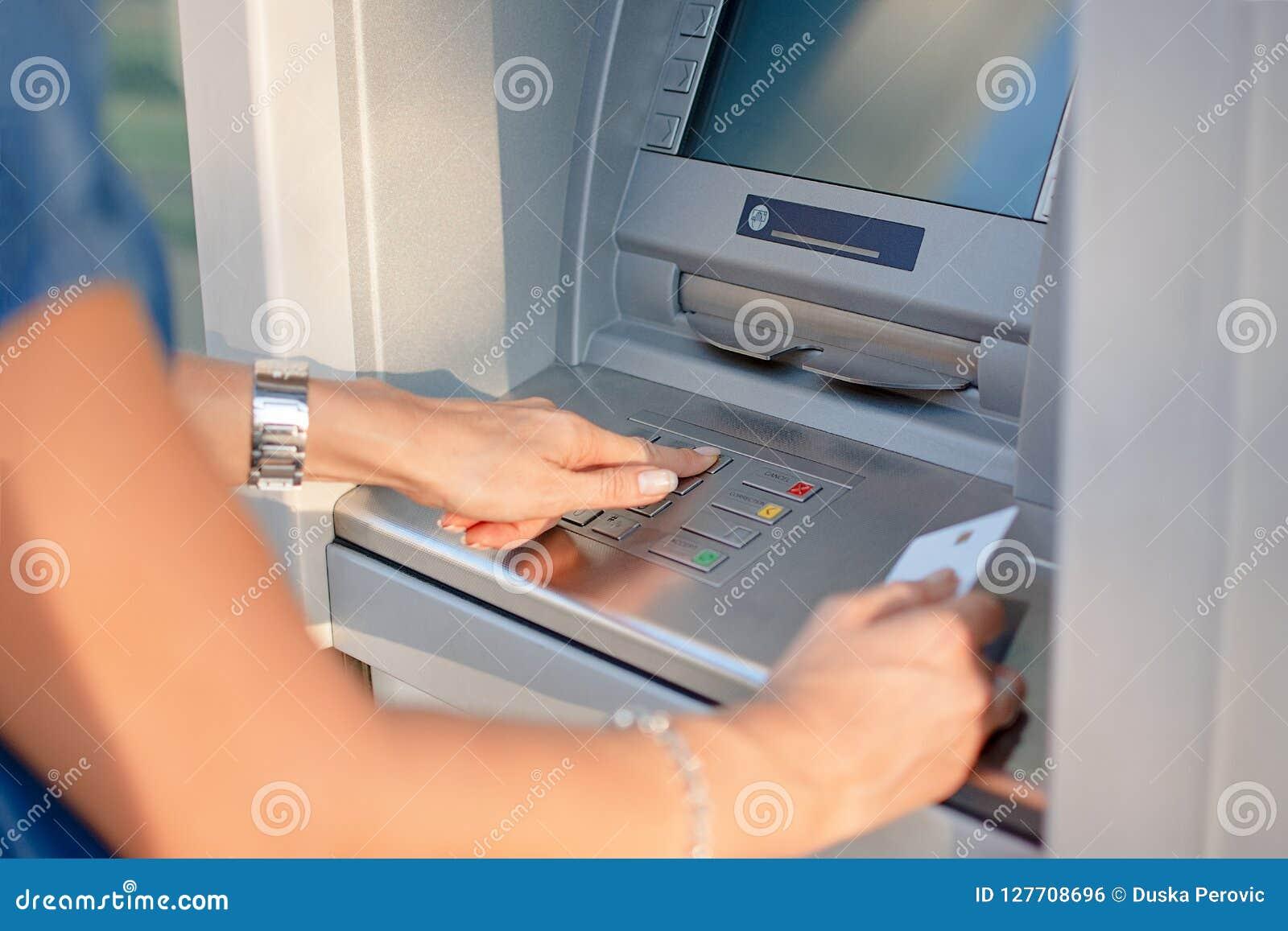 Close-up de Person Using Credit Card To que retira o dinheiro da máquina do Atm