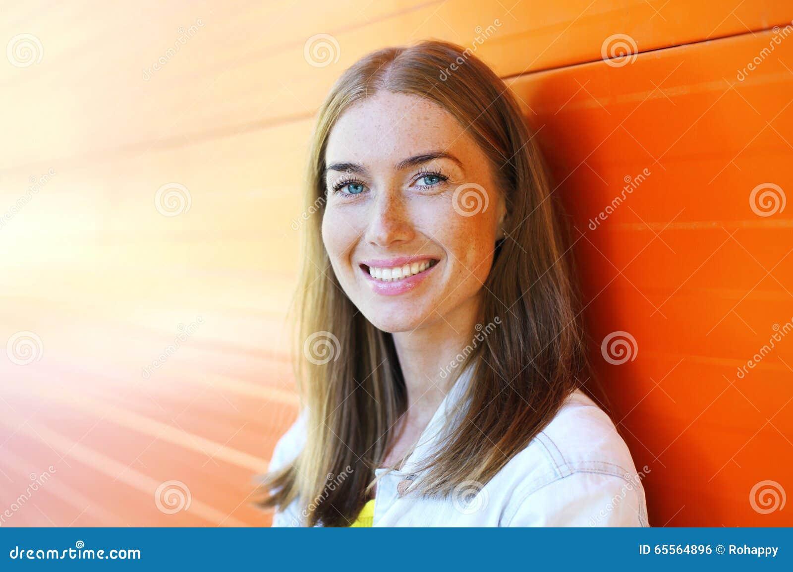 Close up de sorriso bonito feliz da mulher sobre o fundo colorido