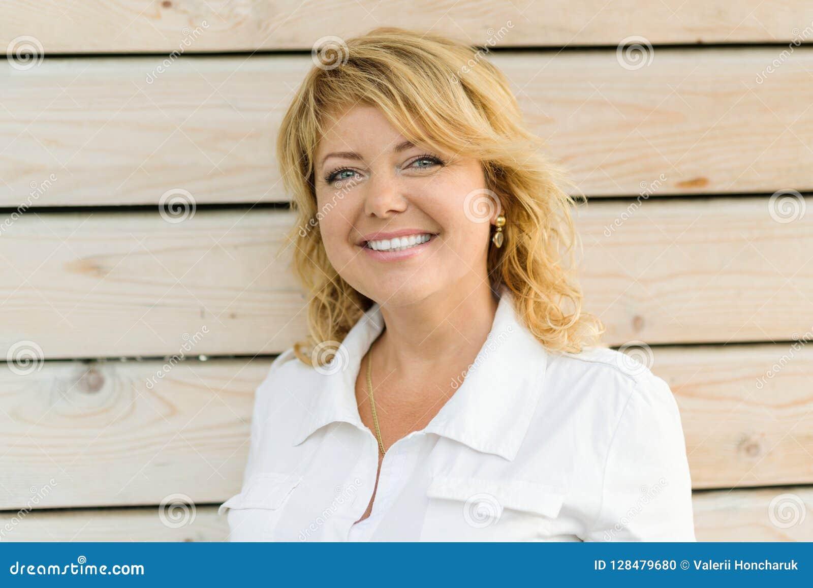 Close-up de sorriso da mulher de meia idade madura positiva do retrato Mulher loura, fundo de madeira exterior