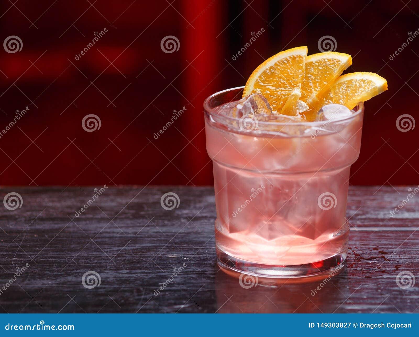 Close up de um cocktail de Fitzgerald no vidro curto, gim, estando no contador da barra, isolado em um fundo claro vermelho