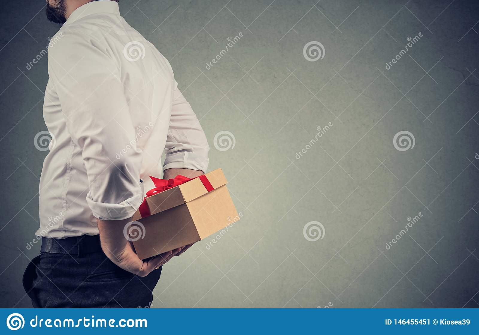 Close up de um homem na camisa branca que retém uma caixa de presente atrás do seu