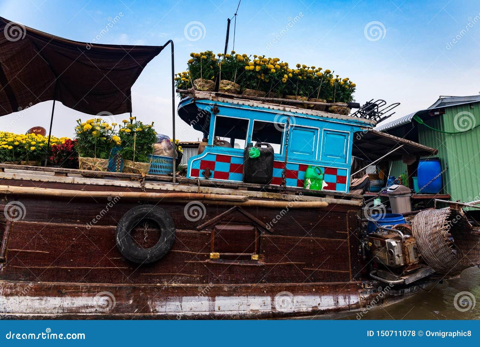 Close-up de um marrom e de um barco azul ou sampana que leva flores amarelas e vermelhas para a celebração do ano novo de Tet, de