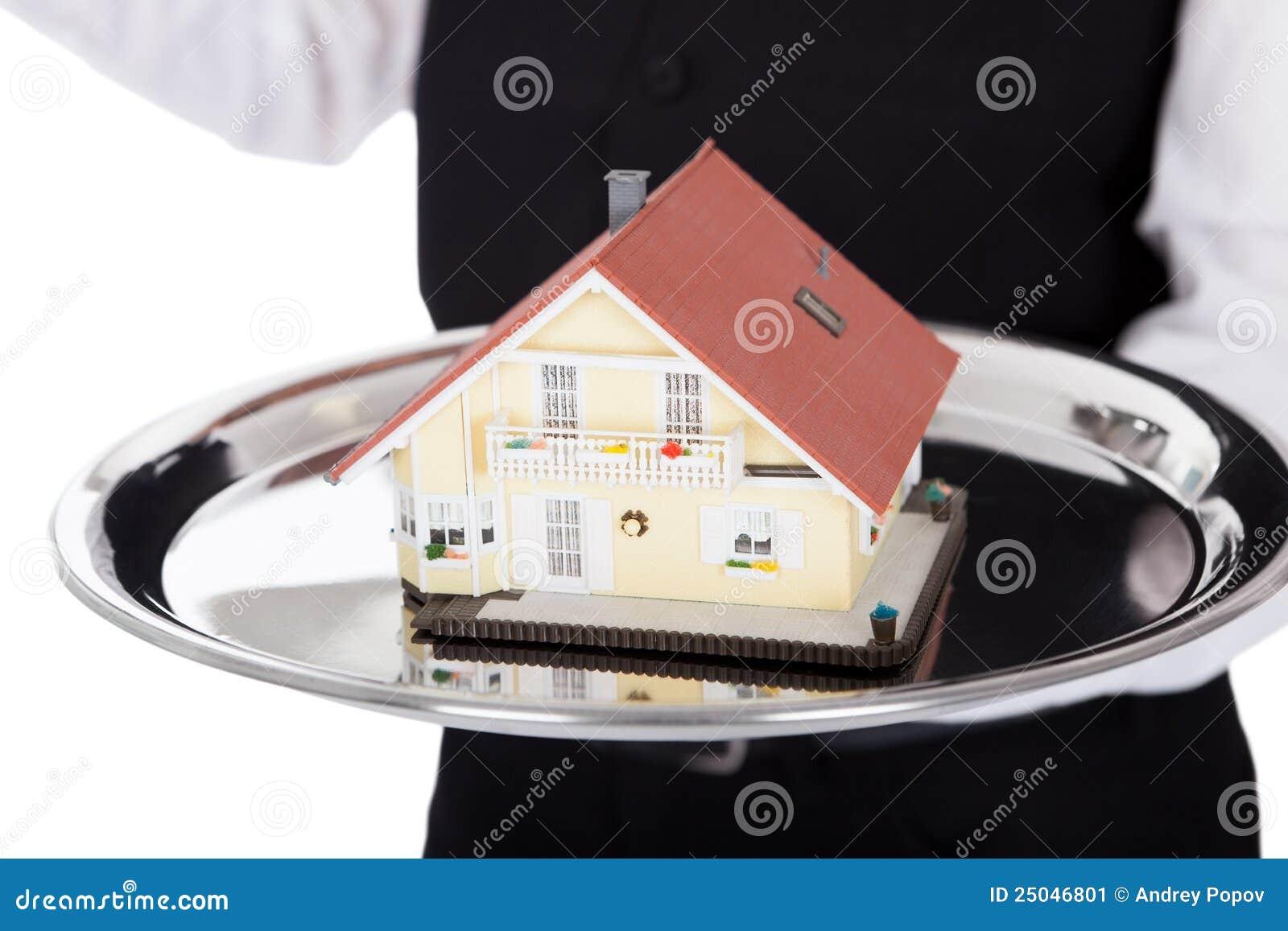 Close-up de um mordomo com modelo de uma casa