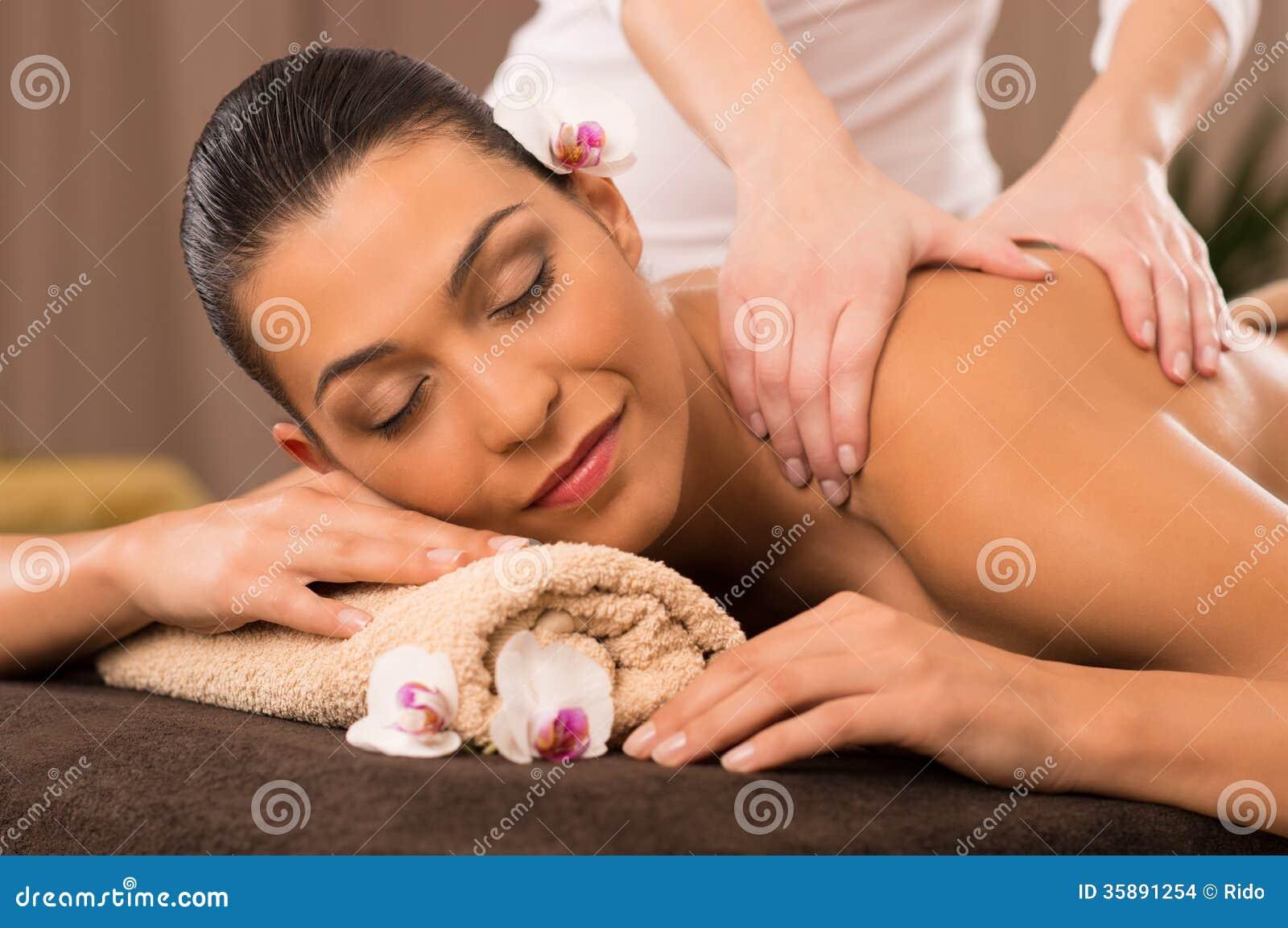 Close-up de uma jovem mulher que recebe a massagem traseira em termas