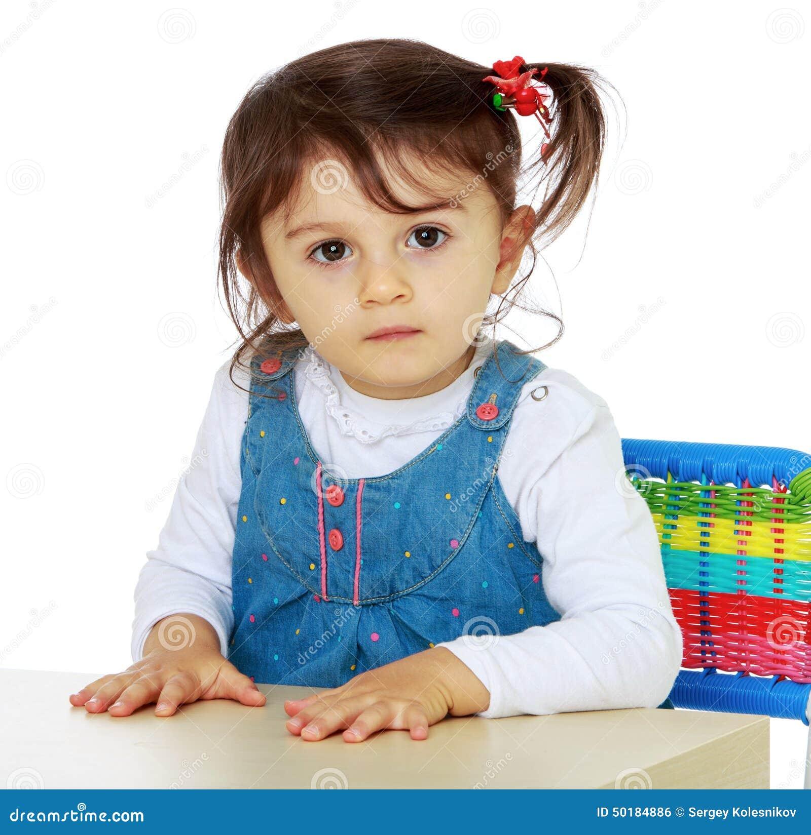 Close up de uma menina bonita que senta-se na tabela Isolado no branco ...