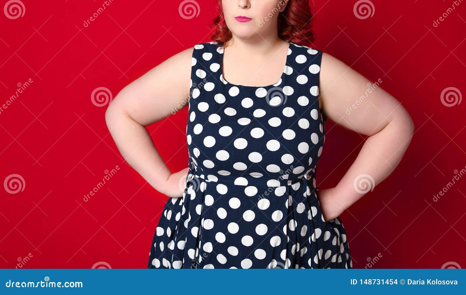 Close up de uma mulher irritada gorda do ruivo que guarda seu mordente ? m?o Menina do Pinup isolada