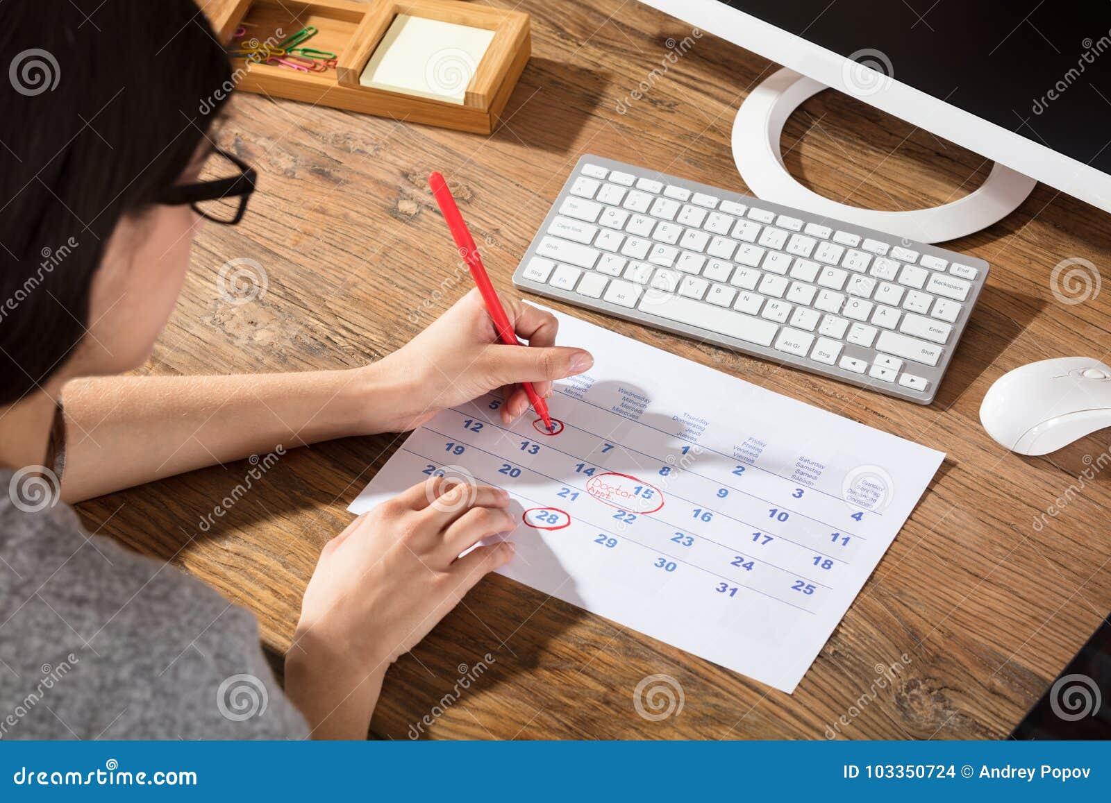 Close-up de uma mulher que circunda a data no calendário