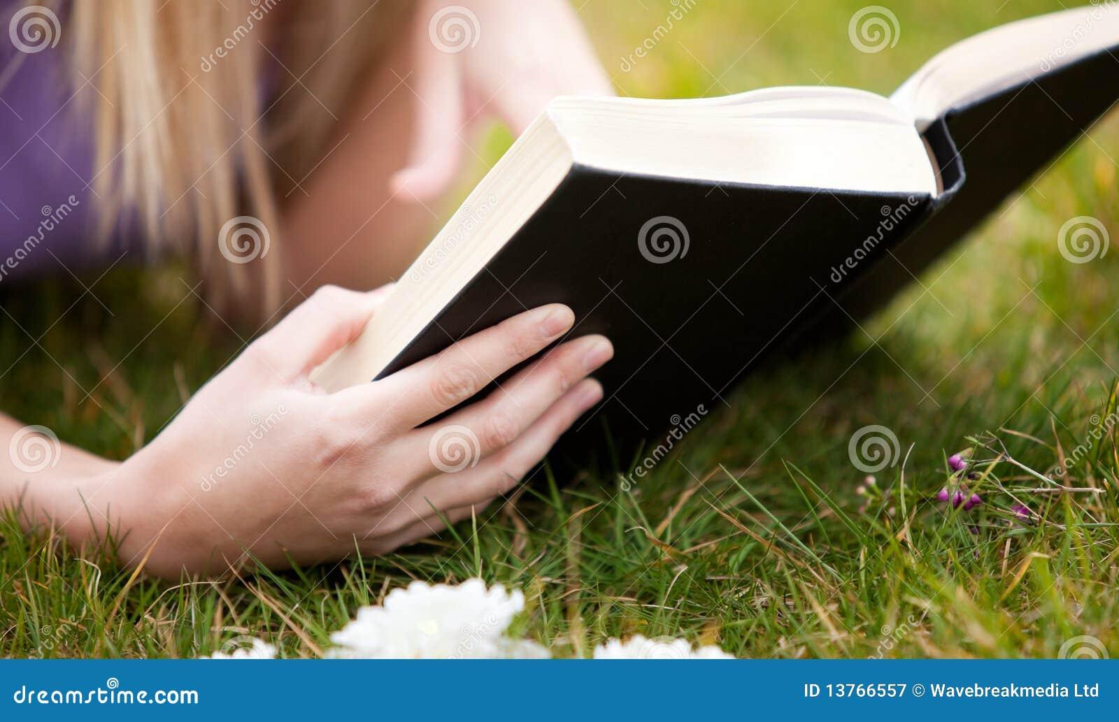 Close-up de uma mulher que lê um livro em um parque