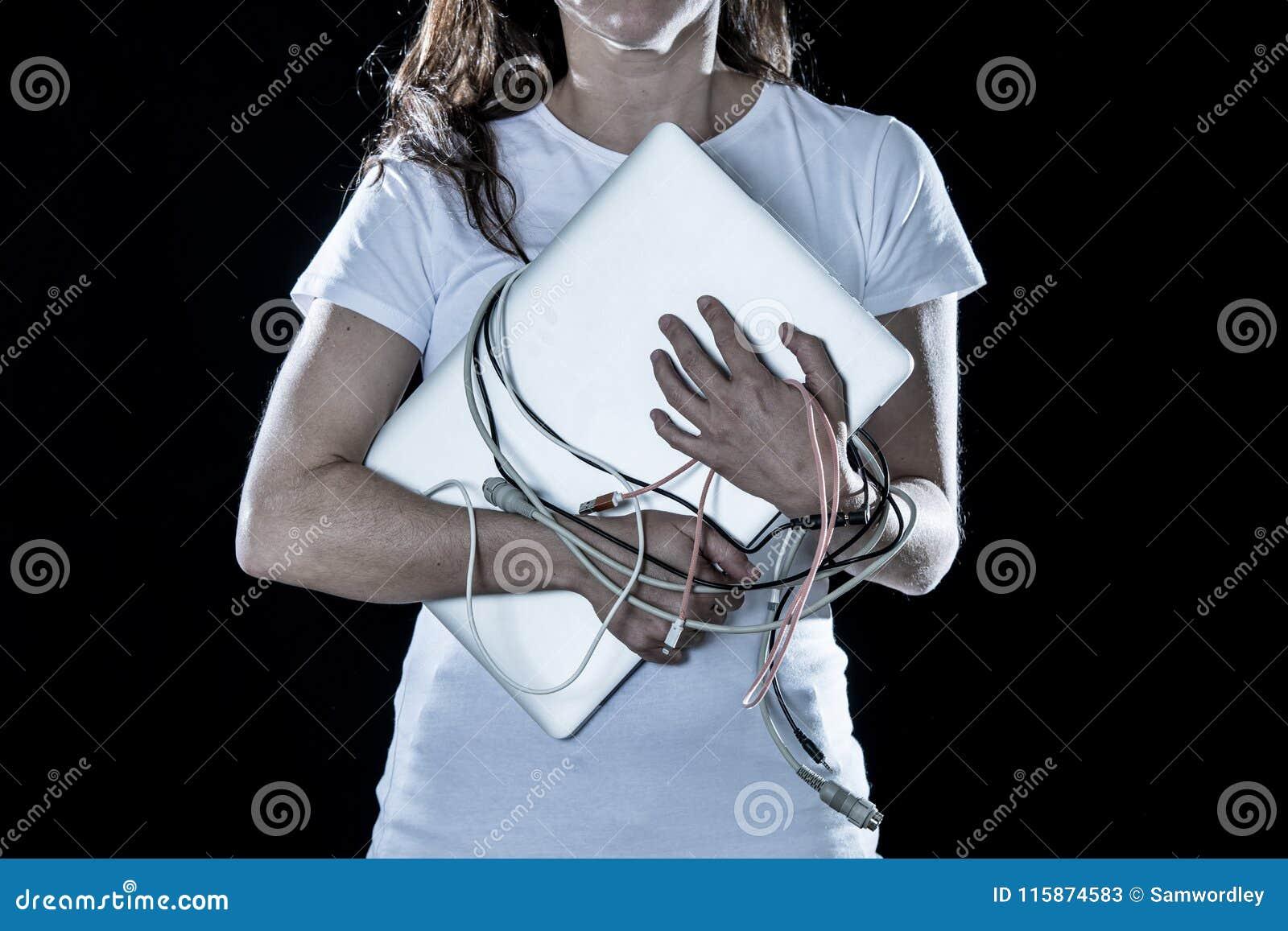 Close up de uma mulher trabalhada excedente que guarda um portátil e cabos no conceito do apego do computador