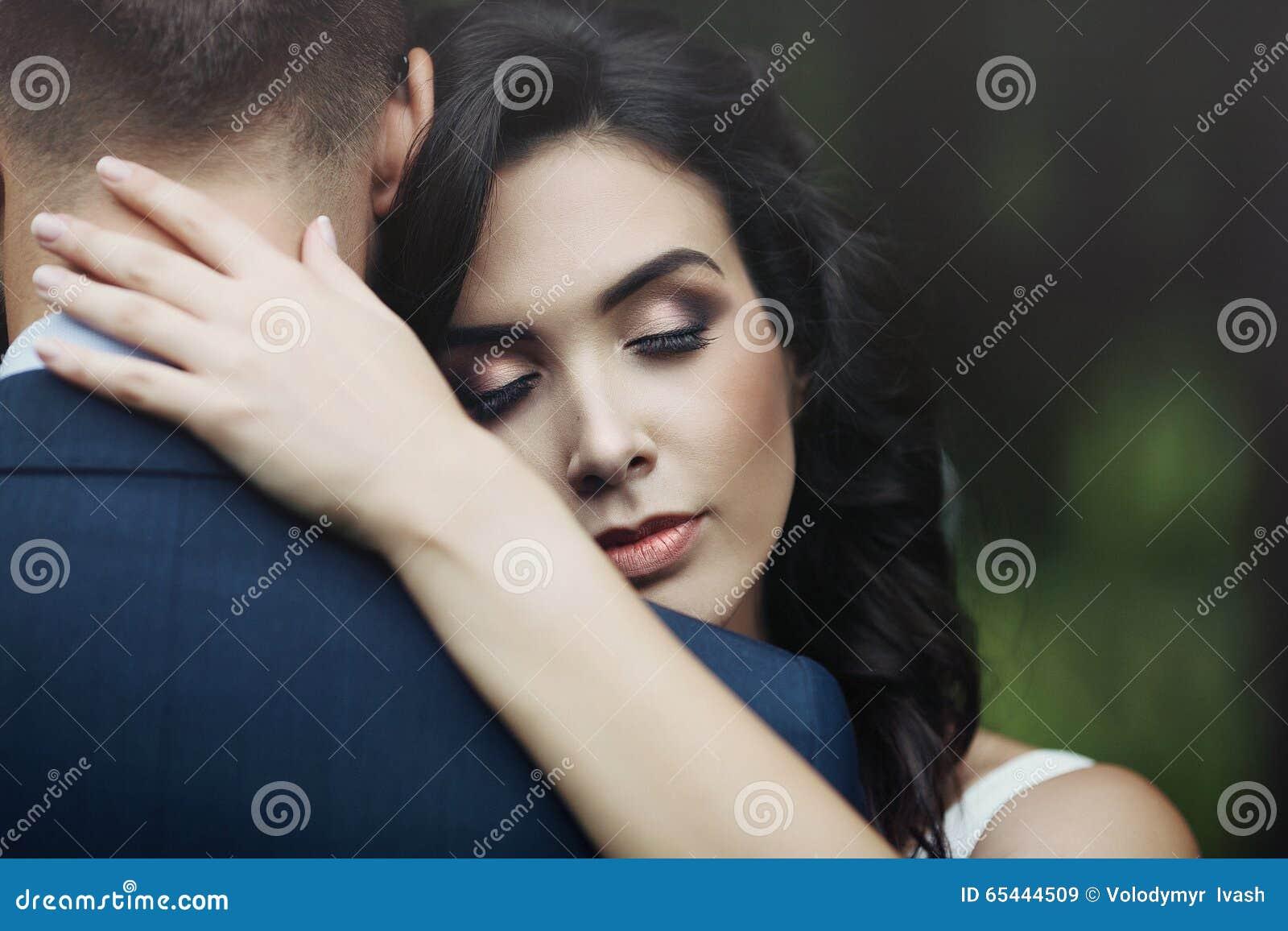 Close up de uma noiva bonita, feliz que abraça o noivo considerável com