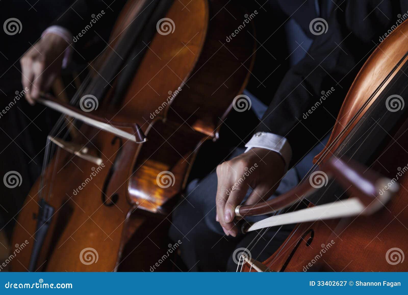 Close-up de uma seção mestra de dois violoncelistas que jogam o violoncelo durante um desempenho