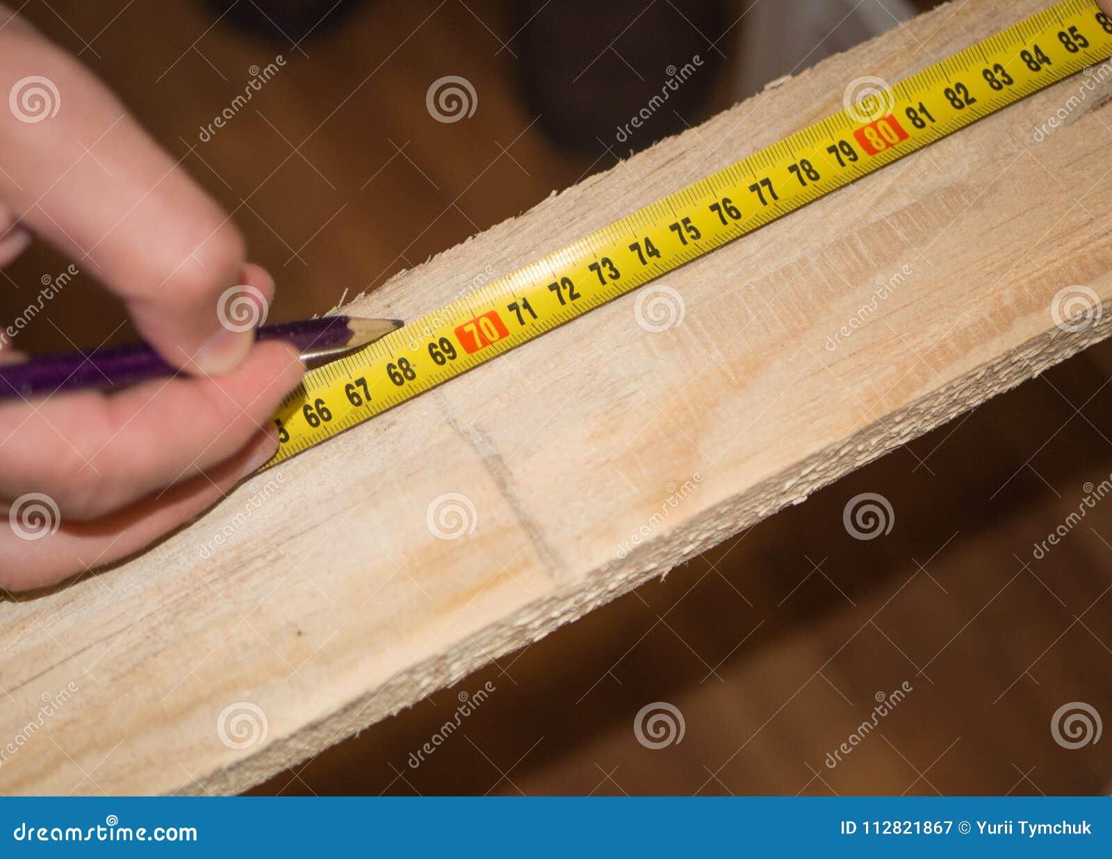 Close up de usar a fita-linha para medir a placa de madeira e para fazer identificar por meio de lápis