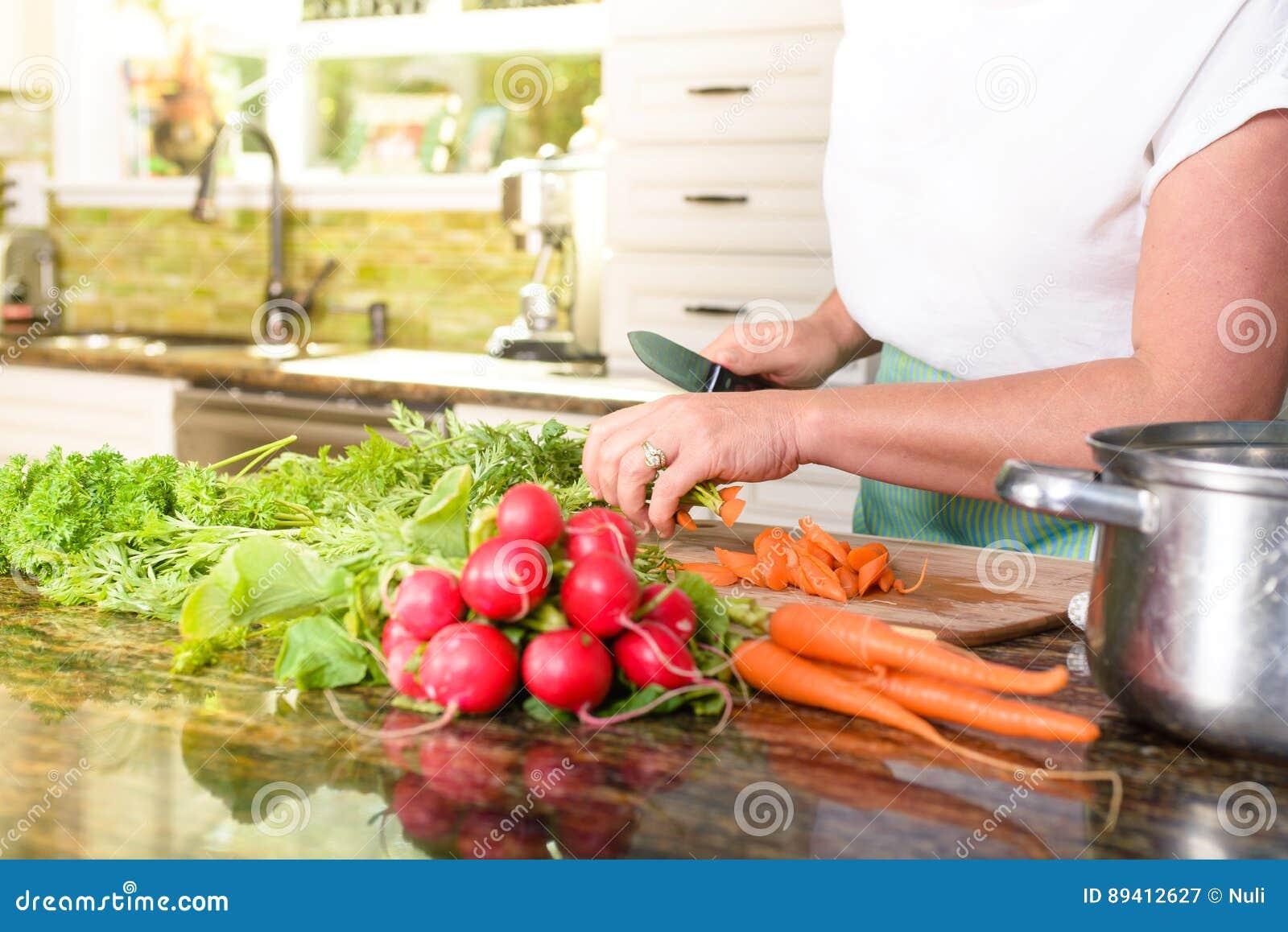 Close-up de vegetais do corte da mulher na cozinha ensolarada