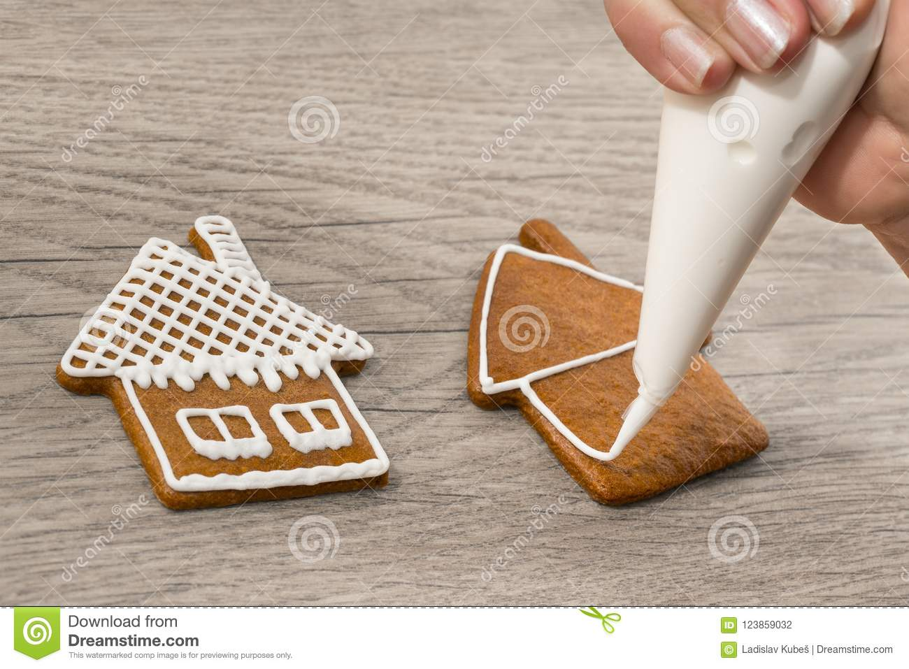 Close-up of decorating sweet gingerbreads in house shape