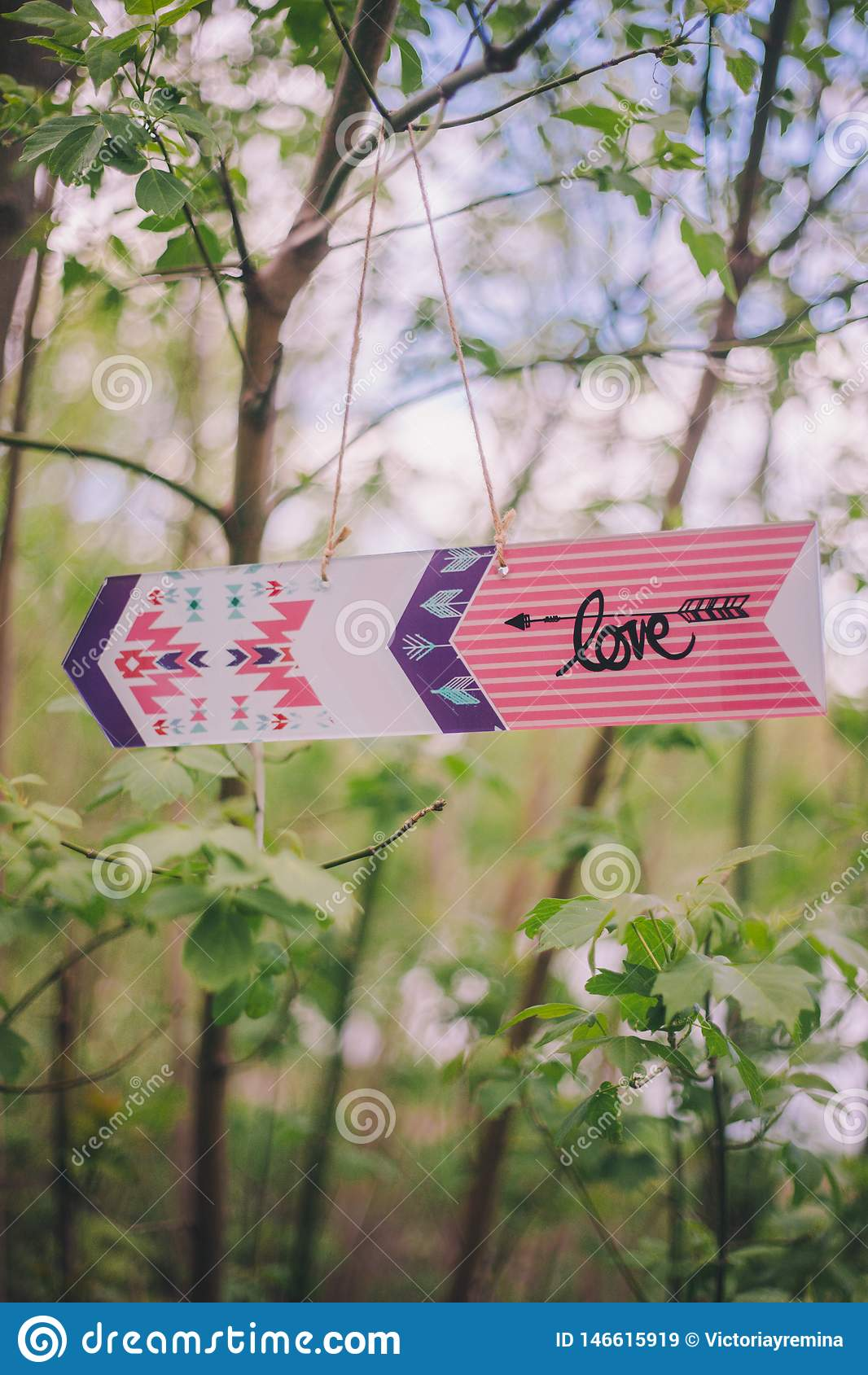 Close-up decorative arrow-pointer with inscription «love» hanging on branch tree on nature