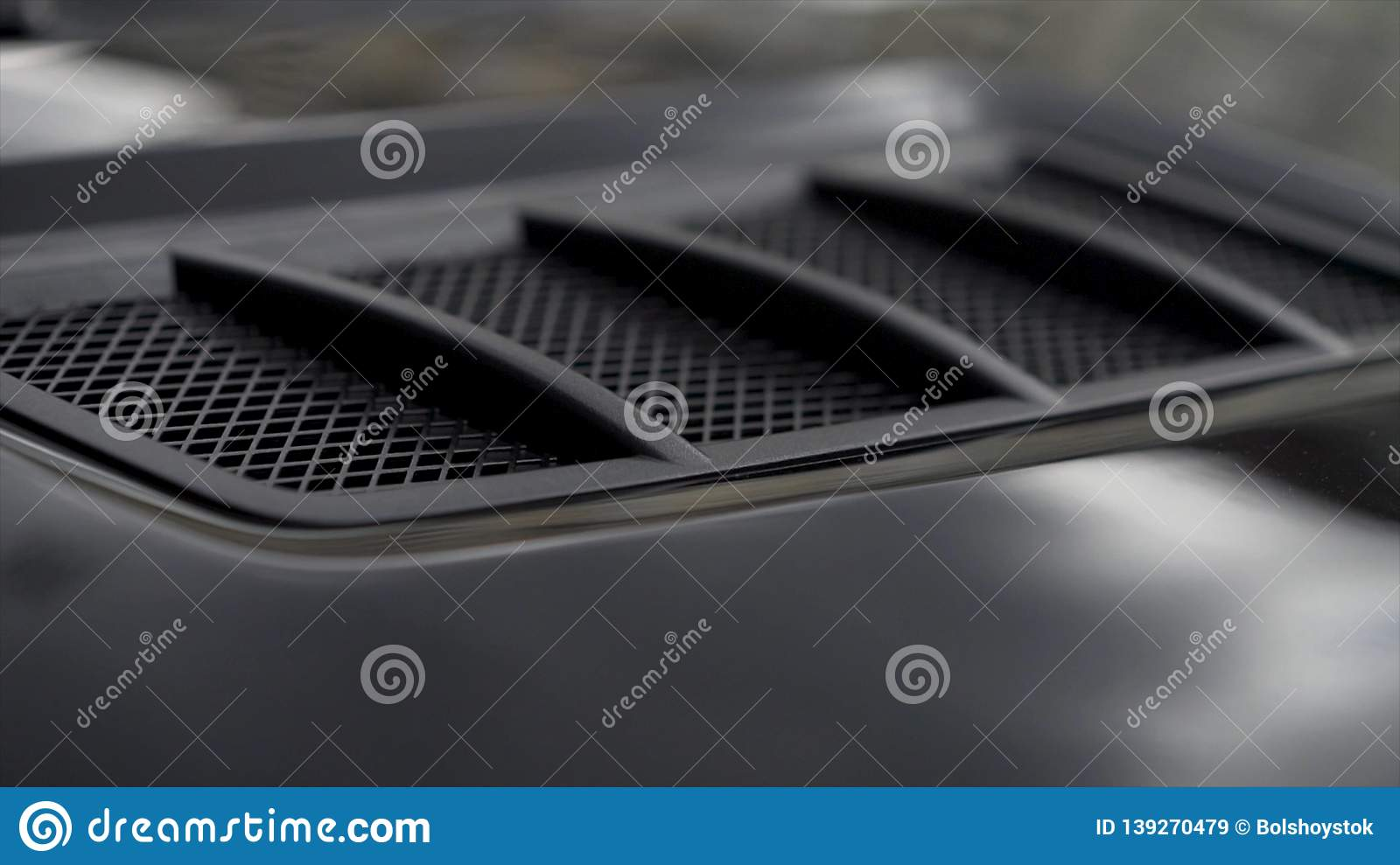 Close up for detail of air vents on the bonnet of a modern black car. Stock. Car exterior background detail of air