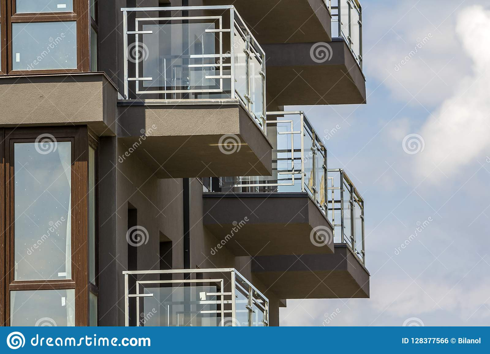 Close-up detail of apartment building wall with balconies and shiny windows on blue sky background.