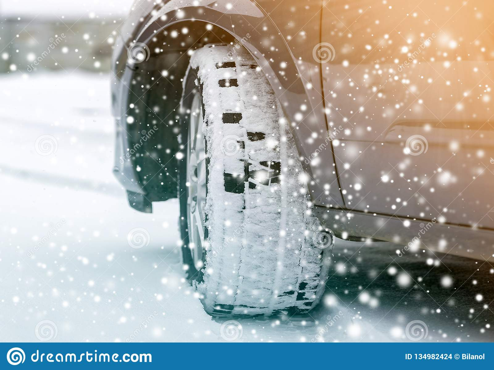 Close up detail car wheel with new black rubber tire protector on winter snow covered road. Transportation and safety concept