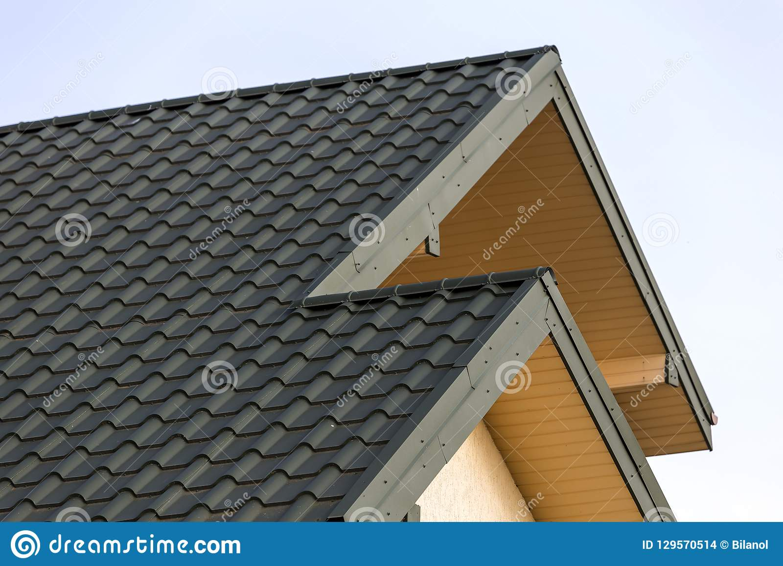 Close-up detail of new modern house top with shingled green roof on clear blue sky background. Professionally done building and co