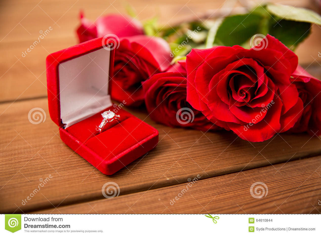 Close Up Of Diamond Engagement Ring And Red Roses Stock