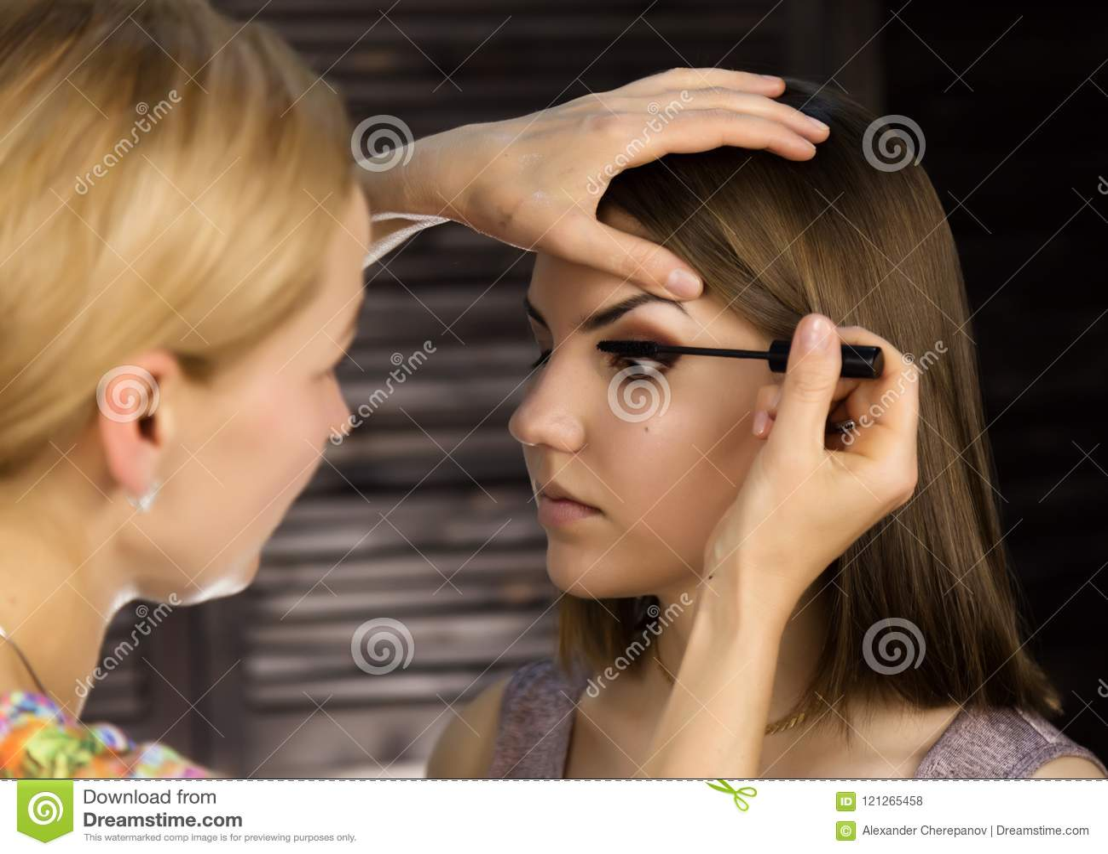 Close-up die van professionele grimeur eyeliner op ooglid toepassen De stilist doet goedmaakt wijfje door eyeliner