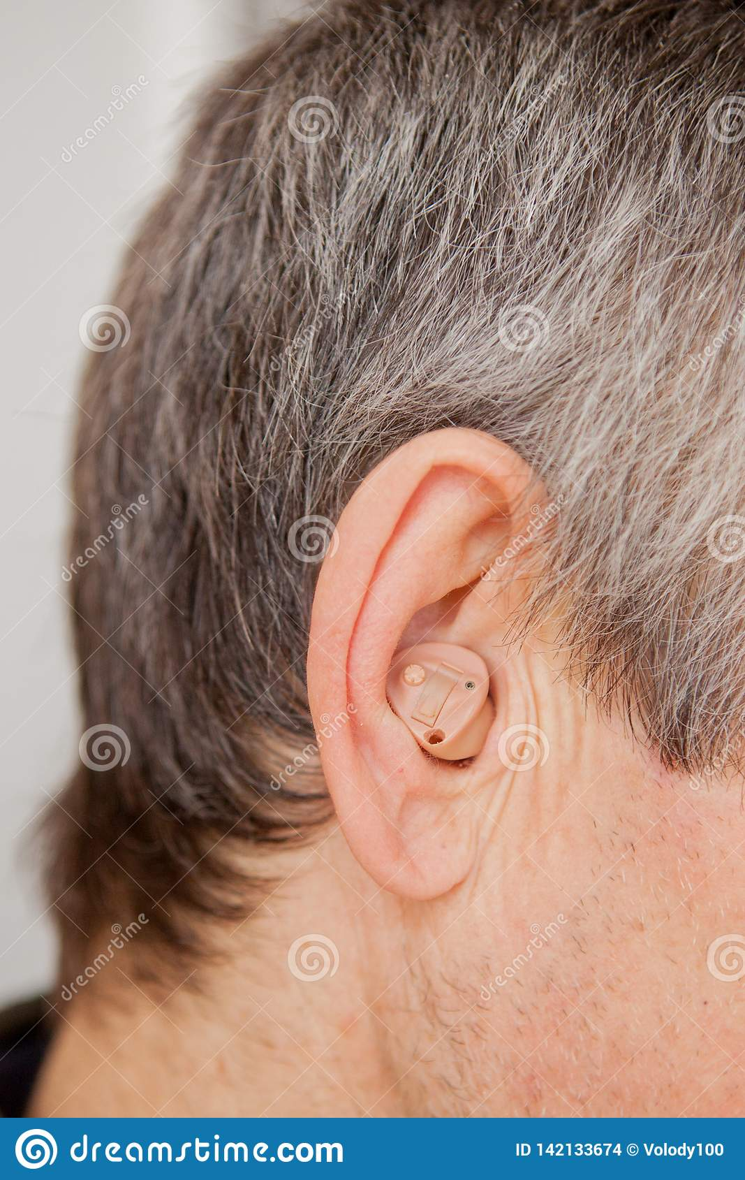 Close-up Digitaal modern gehoorapparaat in het oor van de oude oude mens